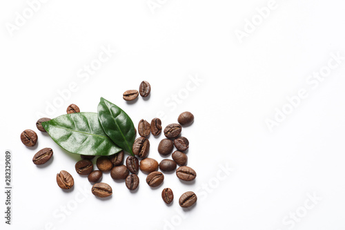 Fresh green coffee leaves and beans on white background, top view © New Africa