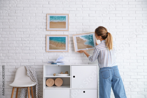 Obraz Decorator hanging picture on white brick wall in room. Interior design - fototapety do salonu