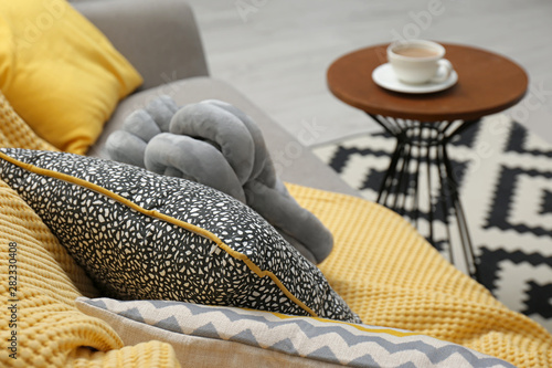 Fényképezés  Soft pillows and yellow plaid on sofa in living room