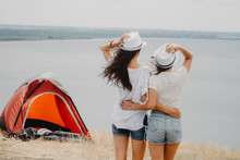 Two Young Girlfriends Are Standing On A Hill Near The Tent With Their Backs Into The Frame, Hugging Each Other At The Waist, Looking Into The Distance Into The River.