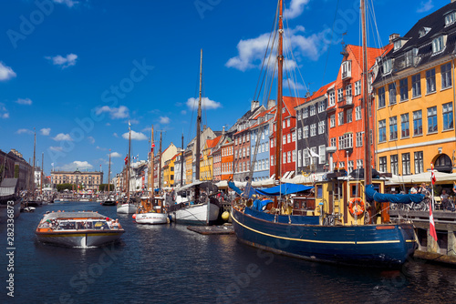 Sightseeing boat sailing by the harbour Nyhavn of Copenhagen Canvas Print