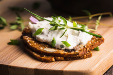 A Delicious Garlic And Chive Cream Cheese Spread On Herbed Crackers Stacked On A Bamboo Cutting Board.
