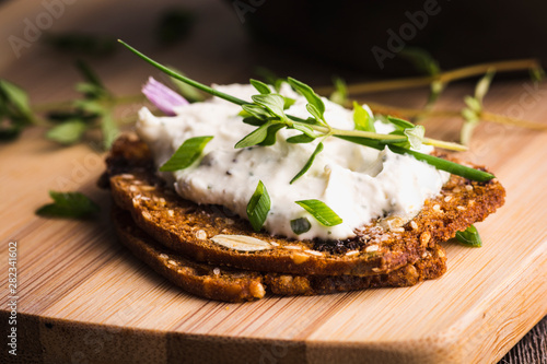 A delicious garlic and chive cream cheese spread on herbed crackers stacked on a bamboo cutting board Tapéta, Fotótapéta