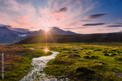 Deurstickers Lichtroze Wallpaper norway landscape nature of the mountains of Spitsbergen Longyearbyen Svalbard on a flowers polar day with arctic summer in the sunset