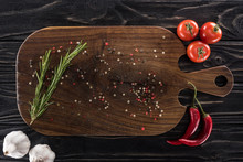 Top View Of Wooden Cutting Board With Spices, Greenery, Cherry Tomatoes, Chili Peppers And Garlics