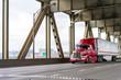 canvas print picture - Bright red big rig semi truck transporting cargo in refrigerator semi trailer moving on the two levels bridge across Willamette River in Portland