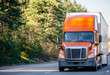 canvas print picture - Orange big rig semi truck transporting cargo in semi trailer running on the road with trees