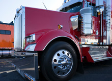 Shiny Red Big Rig Semi Truck Tractor With Chrome Parts And Accessories Standing On Truck Stop Parking Lot