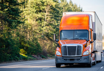 Orange big rig semi truck transporting cargo in semi trailer running on the road with trees