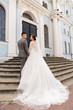 canvas print picture - Wedding couple. Beautiful bride in a luxurious white wedding dress and elegant groom look at each other near the church. Stylish newlywed couple. Marriage concept