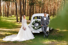 "Wedding Couple Posing Near Wedding Car With Bouquet And The Word ""Wedding"". Just Married Car For The Bride And Groom"