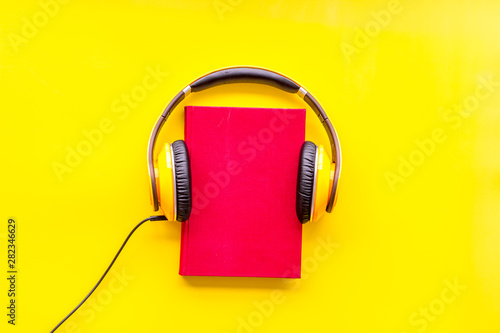 listen to audio books with headphone on yellow background flatlay Wallpaper Mural