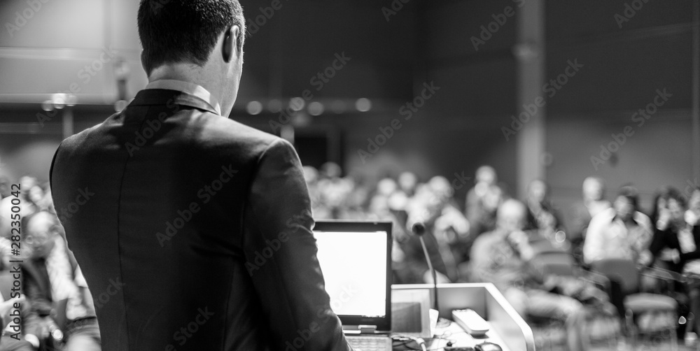 Fototapeta Speaker giving a talk on corporate business conference. Unrecognizable people in audience at conference hall. Business and Entrepreneurship event. Black and white image.