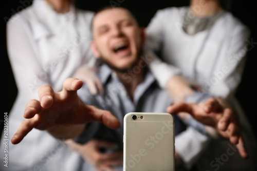 Obraz Emotional man reaching for smartphone while medical workers holding him back on black background, closeup. Addiction concept - fototapety do salonu