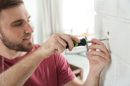 Canvas Print Young working man using screwdriver at home