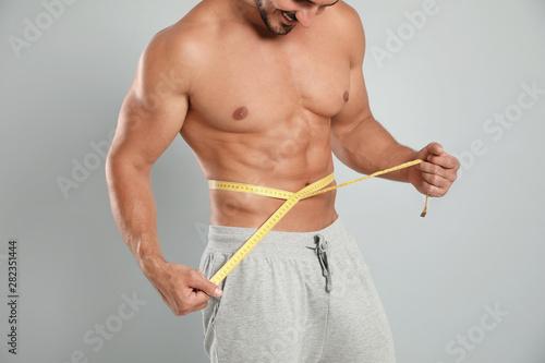 Naklejka premium Młody człowiek szczupły ciało za pomocą miarki na szarym tle, widok zbliżenie