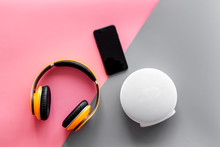 Portable Wireless Speakers, Phone And Headphones For Music Listening On Pink And Gray Background Top View