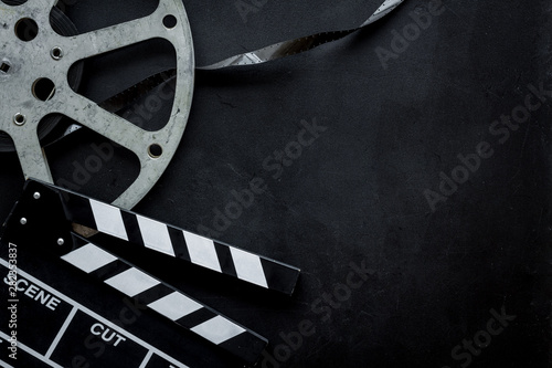 Photo Go to the cinema with film type and clapperboard on black background top view mo