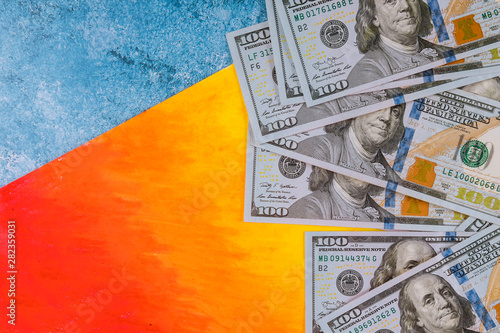 Cuadros en Lienzo  US dollars money on blue and orange background.