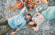 Summer Beach Picnic At Sunset. Young Couple Lying On Striped Blanket, Looking At Each Other At Weekend Picnic Outdoor At Seaside With Sparkling Wine, Fresh Fruit And Tray Of Tasty Appetizers, Top View