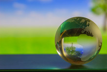 World Globe Crystal Glass Reflect In Green Wide Grassland, Tree And Blue Sky With Clouds Gloss On Table Beside The Window. Global Business And Economy. Environmental Conservation Or Ecology.
