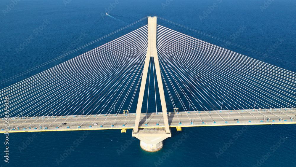 Aerial drone photo of world famous cable suspension bridge of Rio - Antirio Harilaos Trikoupis, crossing Corinthian Gulf, mainland Greece to Peloponnese, Patras