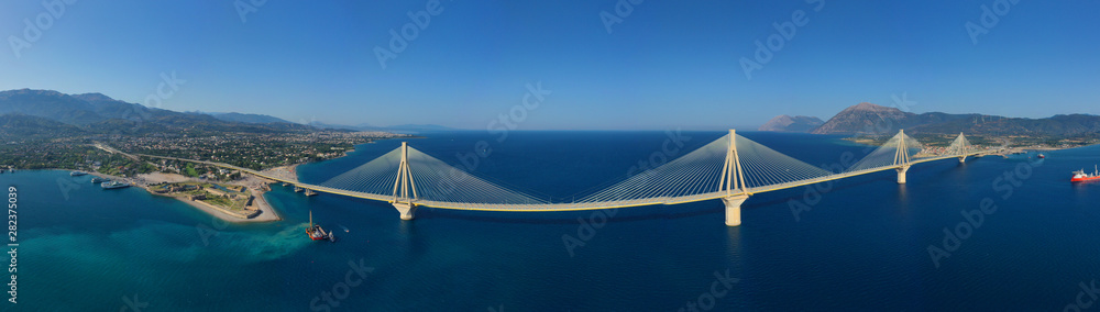 Fototapeta Aerial drone panoramic photo of world famous cable suspension bridge of Rio - Antirio Harilaos Trikoupis, crossing Corinthian Gulf, mainland Greece to Peloponnese, Patras