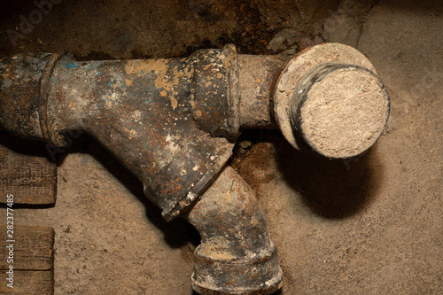 Worn out rusty water pipe in a concrete wall Canvas Print