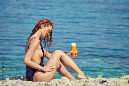 sexy young woman on the beach applying sun cream