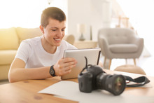 Teenage Photographer With Tablet Computer At Home