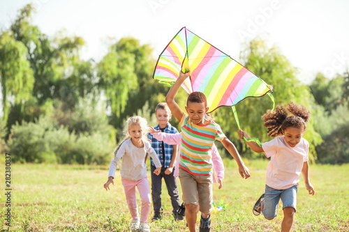 Group of happy children with kite in park Wallpaper Mural