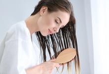Beautiful Young Woman Brushing Hair After Washing At Home