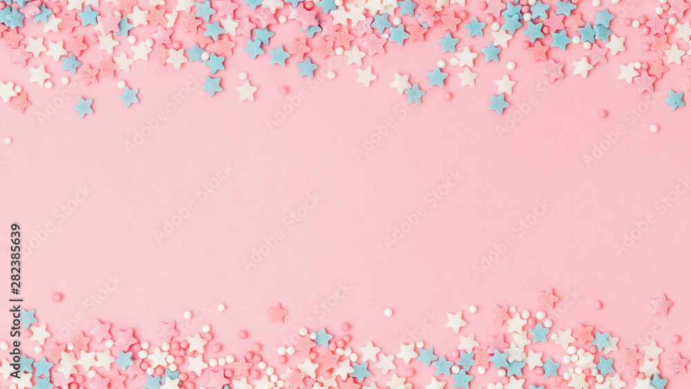 Fototapety, obrazy: Festive border frame of colorful pastel sprinkles on pink background with copy space in center. Sugar sprinkle dots and stars, decoration for cake and bakery. Top view or flat lay. Banner