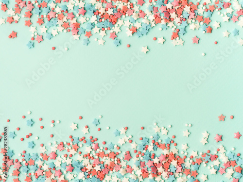 Fototapeta Festive border frame of colorful pastel sprinkles on blue background with copy space in center. Sugar sprinkle dots and stars, decoration for cake and bakery. Top view or flat lay. obraz na płótnie