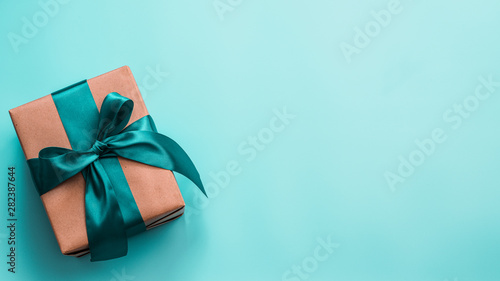 Fotografía Gift box in craft wrapping paper and green satin ribbon on turquoise blue background, copy space right