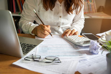 Budget Planning Concept, Accountant Is Calculating Company's Annual Tax. Calendar 2021 And Personal Income Tax Forms For Those Who Have Income Under US Law Placed On Office Desk.