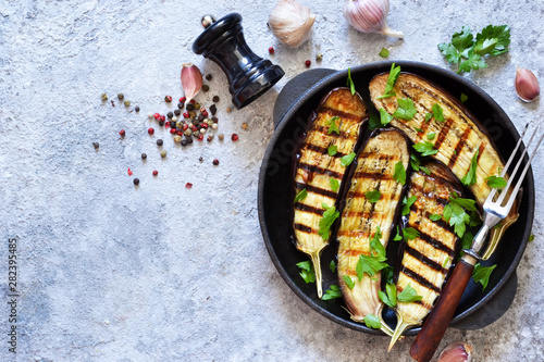 Spicy eggplant grilled in a cast-iron frying pan on a concrete background Canvas Print