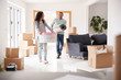 Smiling Couple Carrying Boxes Into New Home On Moving Day