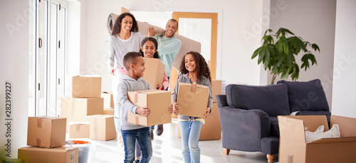 Fotografie, Obraz Smiling Family Carrying Boxes Into New Home On Moving Day