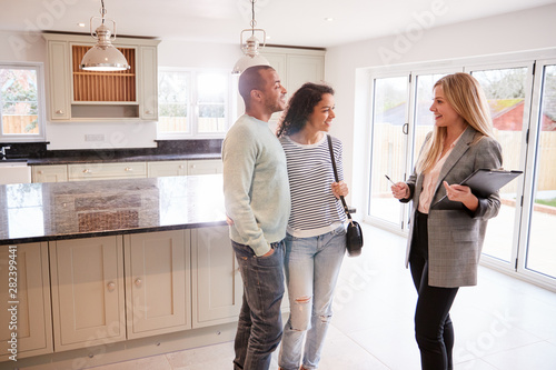 Female Realtor Showing Couple Interested In Buying Around House Wallpaper Mural