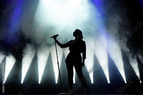 Valokuva  Vocalist singing to microphone. Singer in silhouette