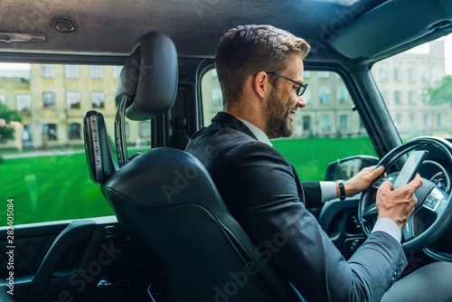 Poster Individuel Handsome young businessman looking on his smart phone while sitting on the front seat and driving a car