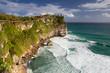 Uluwatu cliff with sea waves and blue sky. Uluwatu Temple is a Balinese Hindu sea temple located in Uluwatu.