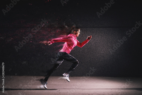 obraz PCV Side motion view of attractive sporty athlete running girl in sportswear at the street in front of the grey wall.