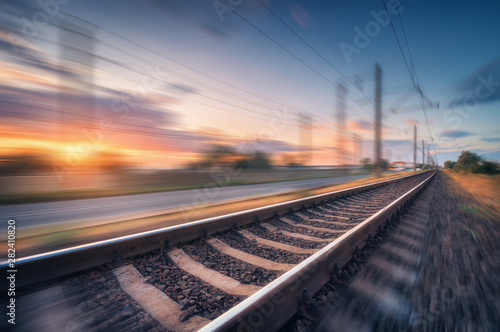Fotomural  Railroad and beautiful blue sky with clouds at sunset with motion blur effect in summer