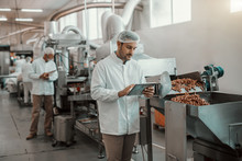 Young Caucasian Serious Supervisor Evaluating Quality Of Food In Food Plant While Holding Tablet. Man Is Dressed In White Uniform And Having Hair Net.