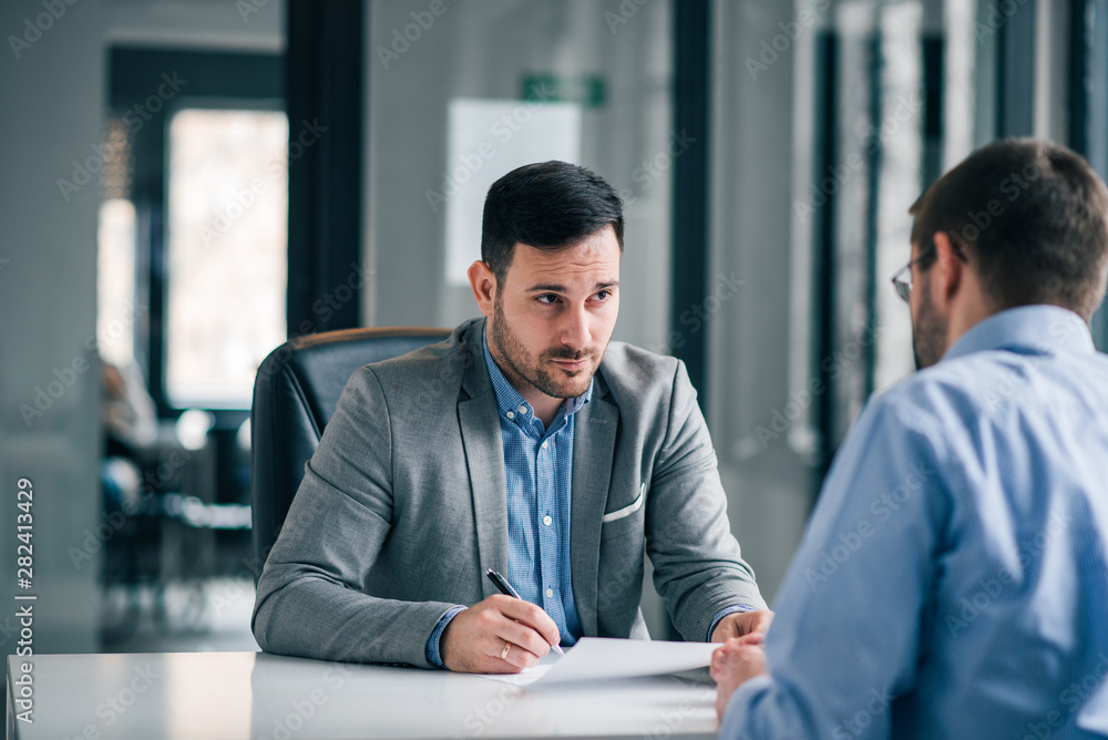 Fototapeta Handsome businessman having pensive look, feeling doubtful about signing contract.
