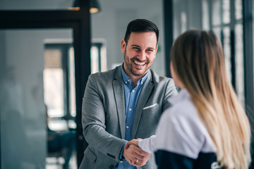 Smiling businessman and young woman shaking hands while standing in the office.