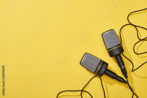 Fotografia  top view of microphones on bright and colorful background with copy space