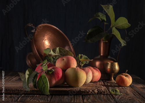 Classical still life with organic natural apples and vintage cooper decoration on old rustic wooden background.
